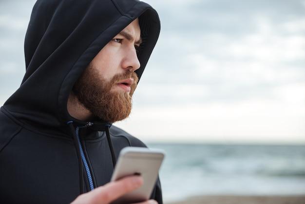 Corridore con il telefono sulla spiaggia di profilo uomo con cappuccio in