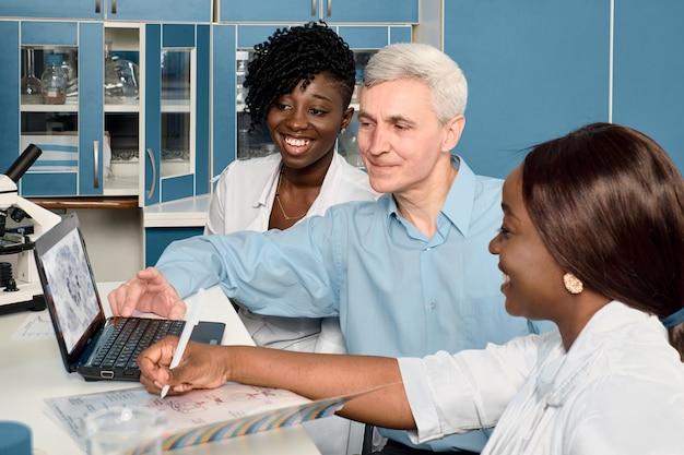 Esecuzione di esami del sangue e dell'acido nucleico sul coronavirus che causa covid-19. rapporto sui progressi nel laboratorio di prova. studentesse di medicina africane, laureate che mostrano dati a un uomo caucasico, capogruppo senor
