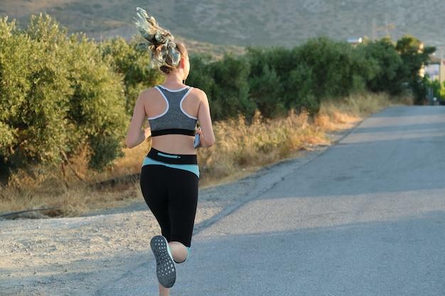 Esecuzione di ragazza fitness in cuffie con smartphone, vista posteriore, copia dello spazio. soleggiata giornata estiva, strada in montagna, stile di vita sano attivo nei giovani