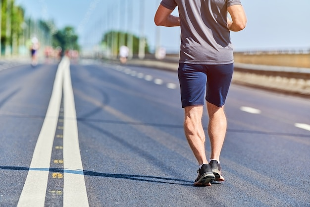 Uomo che corre. uomo atletico che pareggia in abiti sportivi sulla strada della città.