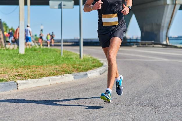 Uomo che corre. uomo atletico che pareggia in abiti sportivi sulla strada della città
