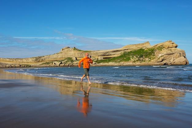 Uomo che corre nella costa dell'oceano, nuova zelanda