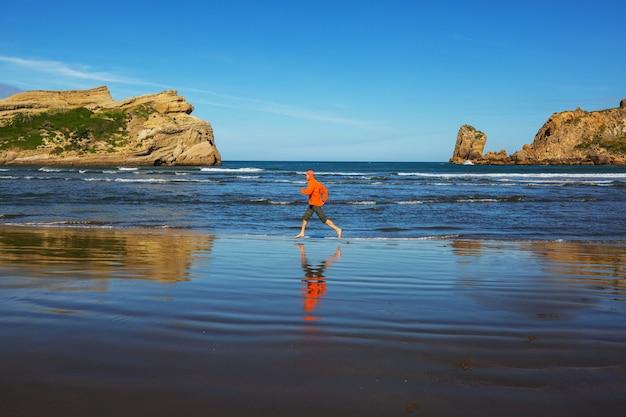 Uomo che corre nella costa dell'oceano