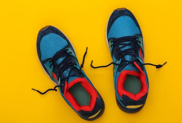 Scarpe da corsa (scarpe da ginnastica) su sfondo giallo. stile di vita sano, allenamento fitness. vista dall'alto
