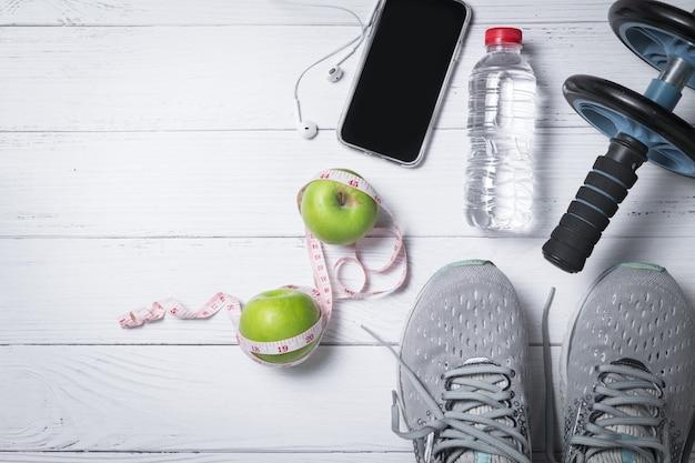 Scarpe da corsa con mele verdi e telefono cellulare vicino alla bottiglia di acqua fresca, esercizio e concetto di dieta
