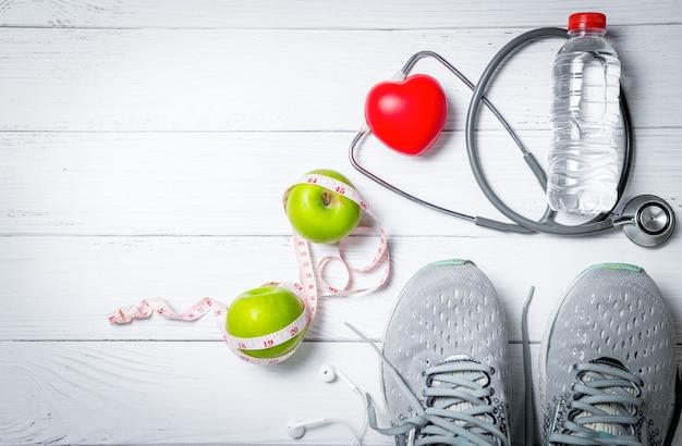 Scarpe da corsa con mele verdi e stetoscopio vicino alla bottiglia di acqua dolce su fondo di legno bianco, esercizio e concetto di dieta