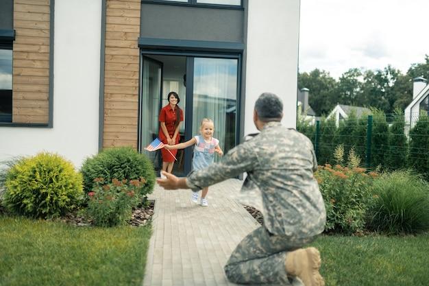 Correre con bandiera. figlia con una piccola bandiera americana che corre verso il padre che finalmente torna a casa