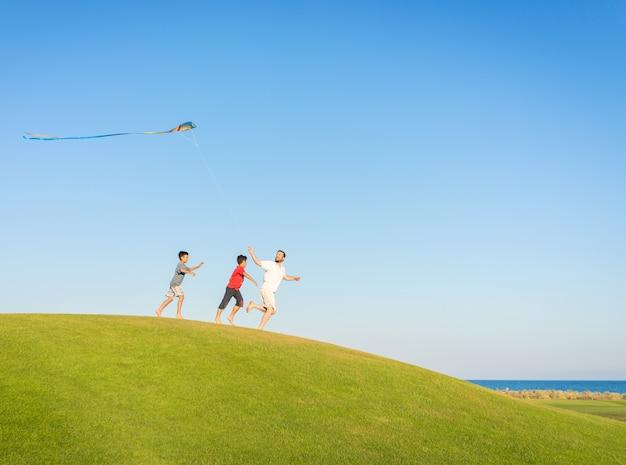 In esecuzione con l'aquilone in vacanza vacanze estive, prato perfetto e cielo in riva al mare