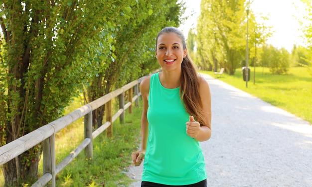 Donna che corre. corridore femminile che pareggia durante l'allenamento all'aperto in un parco. bella ragazza in forma. modello di fitness all'aperto. perdita di peso.