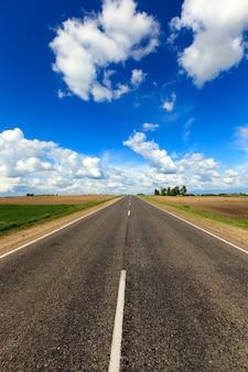 Strada asfaltata rurale in estate. strada attraverso il campo