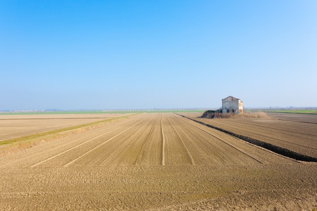 Paesaggio rurale italiano dalla laguna del fiume po. campi arati con linee prospettiche. magazzino abbandonato