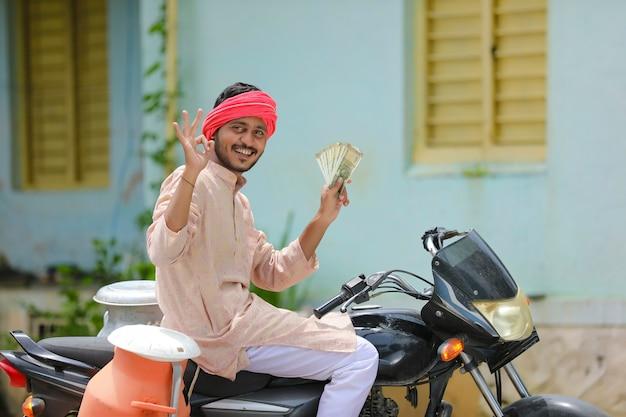 Scena rurale: lattaio indiano seduto in bicicletta e mostrando soldi