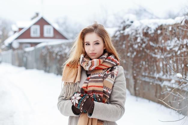 Giovane donna alla moda rurale in un cappotto grigio di inverno in una sciarpa alla moda vintage in guanti di lana caldi è in piedi su una strada innevata nel villaggio vicino a una casa di legno. affascinante ragazza alla moda.