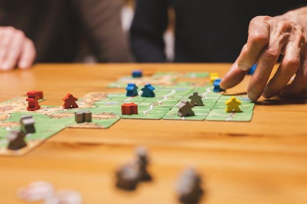 Russia, dicembre 2020: due amici uomini si divertono a giocare al gioco da tavolo carcassonne a tarda sera o di notte. mani maschili e carte da gioco e fiches sul tavolo