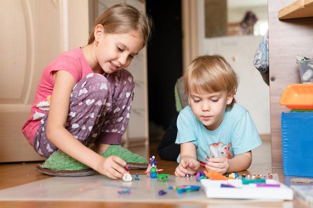 Russia, mosca, ottobre 2020 - due piccoli bambini felici, un bambino di quattro anni e una bambina di sette anni, fratelli o amici a casa sul pavimento insieme a giocare e scolpire con la plastilina