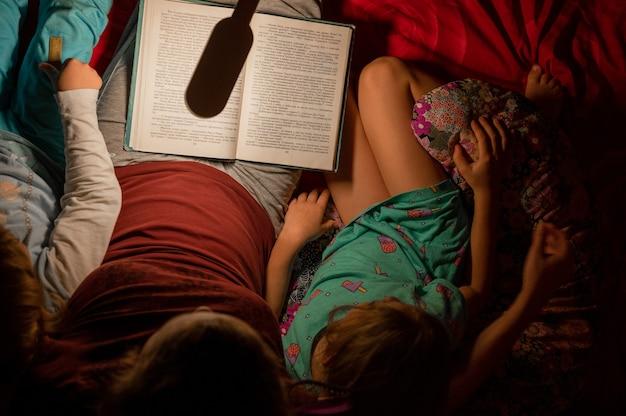 Russia, smakhtino, 3 gennaio 2021 - una madre legge ai bambini piccoli, un figlio maschio e una figlia femmina, un libro di fiabe per la notte, alla luce di una lampada da notte su un letto con cuscini. vista dall'alto