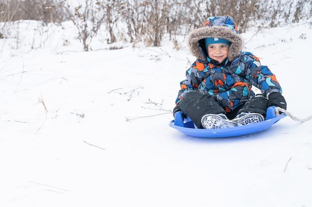 Russia, smakhtino, 27 dicembre 2020 - un felice e carino bambino di cinque anni è attività e divertimento trascorrendo le sue vacanze invernali innevate a cavallo di uno scivolo su una slitta
