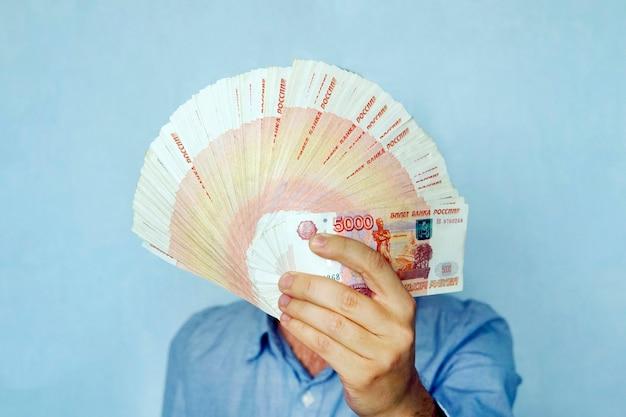 Rubli di banconote russe in mano. 5000 banconote piegate a ventaglio coprono il volto dell'uomo d'affari.