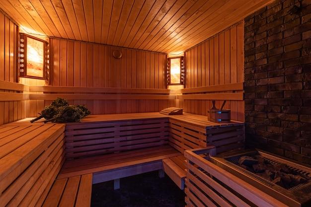 Bagno russo in legno con scope da bagno e divani