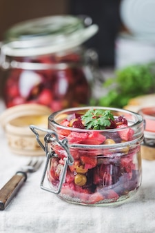 Insalata russa di vinaigrette di barbabietole in un barattolo di vetro con pane di segale, fondo rustico