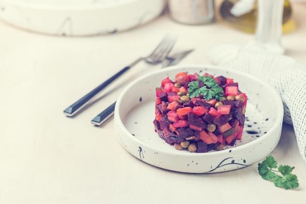 Vinaigrette russa di insalata di barbabietole in un piatto bianco su sfondo chiaro