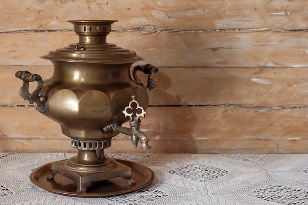 Antico russo d'ottone della samovar su una tavola di legno