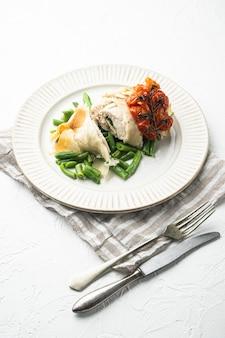 Cucina russa cotolette di pollo ripiene in stile kiev, con pomodorini al forno e fagiolini, su pietra bianca