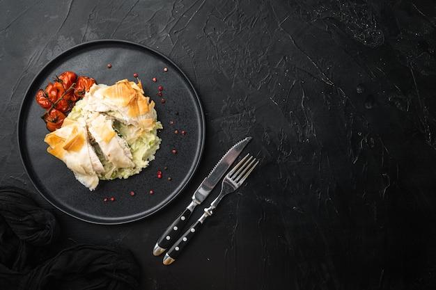 Cucina russa cotolette di pollo ripiene in stile kiev, con pomodorini al forno, purè di patate, su pietra nera