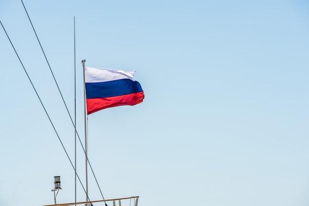 Bandiera russa sull'albero di una barca che va sull'acqua