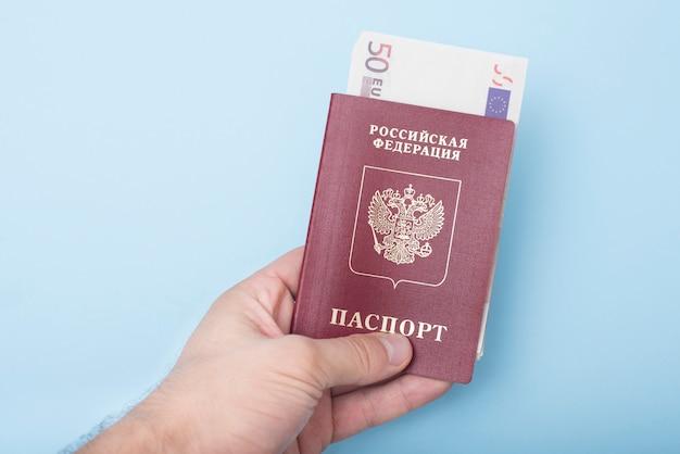 Passaporto internazionale russo con euro in mano all'uomo. blu