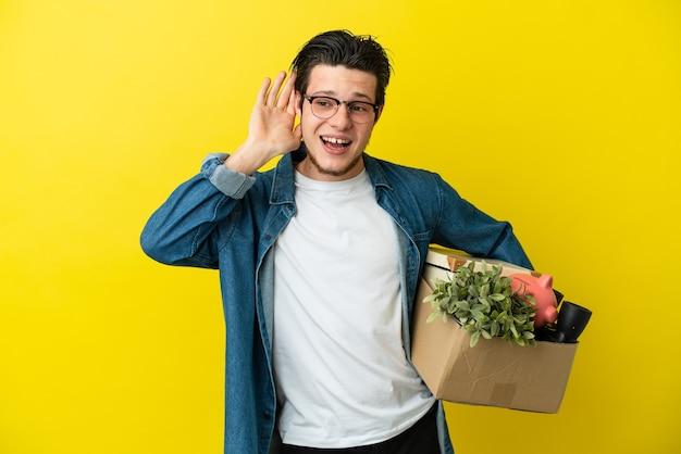 Uomo russo che fa una mossa mentre prende una scatola piena di cose isolate su sfondo giallo ascoltando qualcosa mettendo la mano sull'orecchio