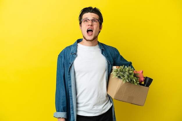 Uomo russo che fa una mossa mentre prende una scatola piena di cose isolate su sfondo giallo guardando in alto e con espressione sorpresa