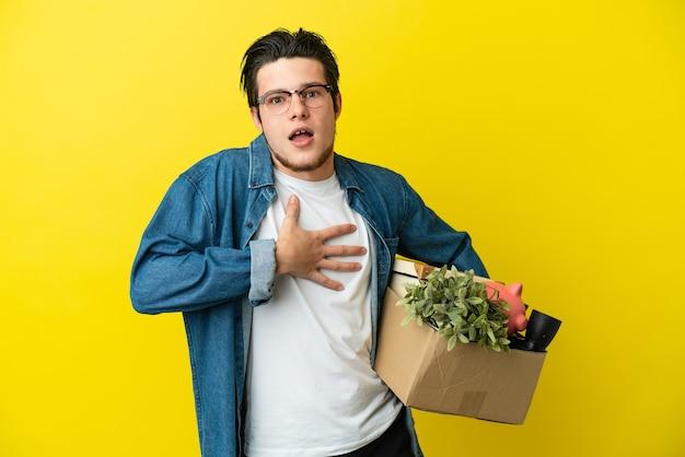 Uomo russo che fa una mossa mentre prende una scatola piena di cose isolate su sfondo giallo sorpreso e scioccato mentre guarda a destra