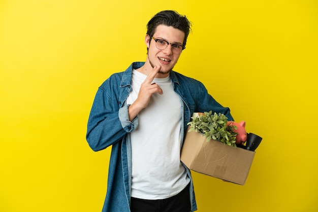 Uomo russo che fa una mossa mentre prende una scatola piena di cose isolate sul muro giallo che guarda in alto sorridendo