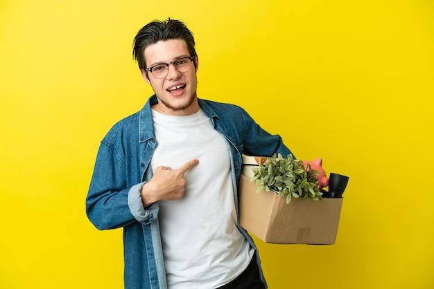 Uomo russo che fa una mossa mentre prende una scatola piena di cose isolate sul muro giallo con un'espressione facciale a sorpresa