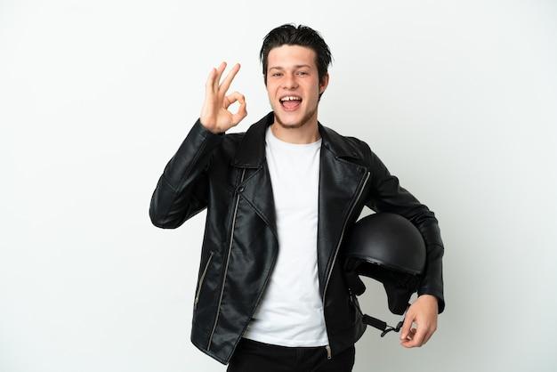Uomo russo con un casco da motociclista isolato sul muro bianco che mostra segno ok con le dita