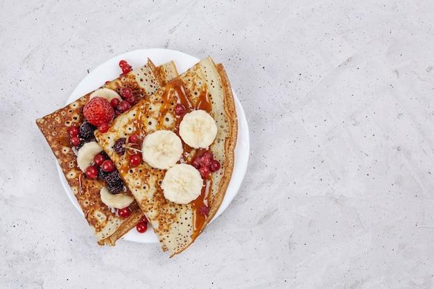 Frittelle russe o blini con frutti di bosco in zolla bianca.