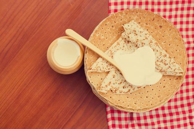 Frittelle russe o blini con panna acida. vista dall'alto. settimana del pancake. shrovetide. spazio per il testo