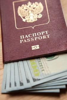 Passaporto russo con banconote da cento dollari sulla scrivania in legno
