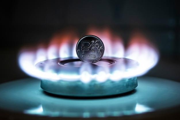 Il rublo russo sta bruciando nel fuoco. bruciatore a gas ardente sullo sfondo di un rubli. il concetto l'aumento del prezzo del gas in russia. fornitura di gas costosa. concentrati sulla moneta