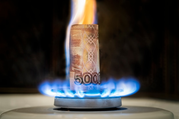 Il rublo russo sta bruciando nel fuoco. concetto l'aumento del prezzo del gas in russia. una banconota di 5000 rubli brucia nel fuoco su una stufa a gas. fornitura di gas costosa