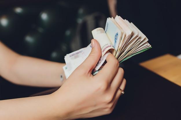 Rubli russi nella mano di un ventilatore. mano maschile che tiene molte delle banconote russe. il trasferimento di denaro.
