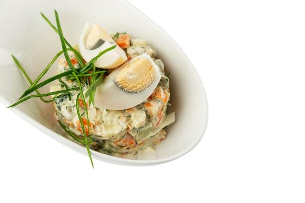 Insalata russa olivier in un piatto bianco. un tradizionale spuntino invernale per le vacanze. avvicinamento. isolato su sfondo bianco. spazio per il testo.