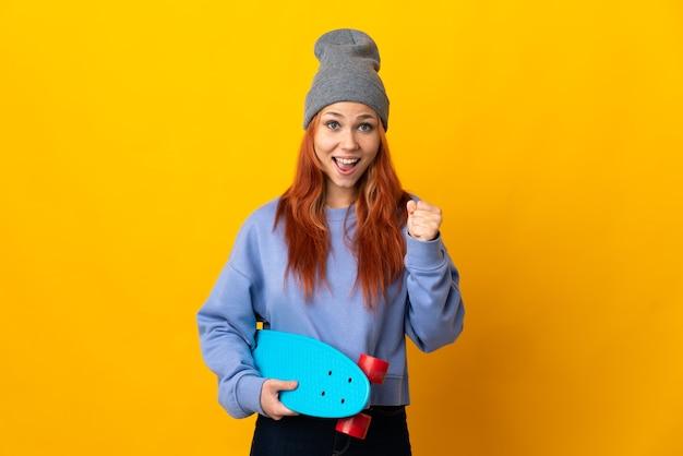 Donna russa del pattinatore isolata su giallo che celebra una vittoria nella posizione del vincitore