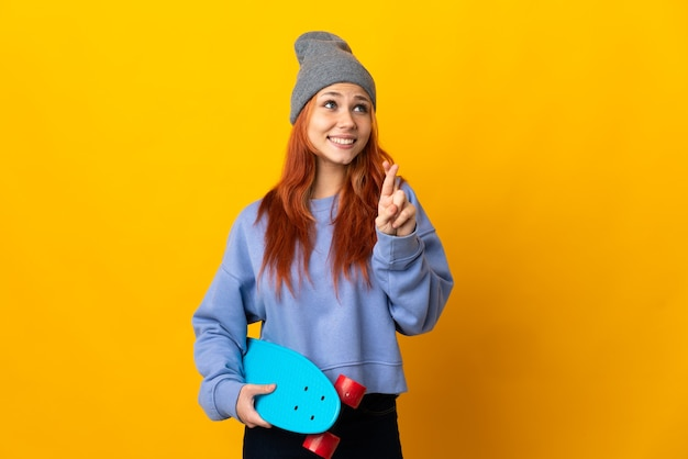 Donna russa pattinatrice isolata su giallo con le dita incrociate e che desiderano il meglio