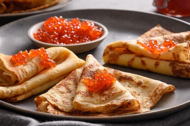 Frittelle sottili russe o blini con caviale rosso su fondo bianco. vista dall'alto.