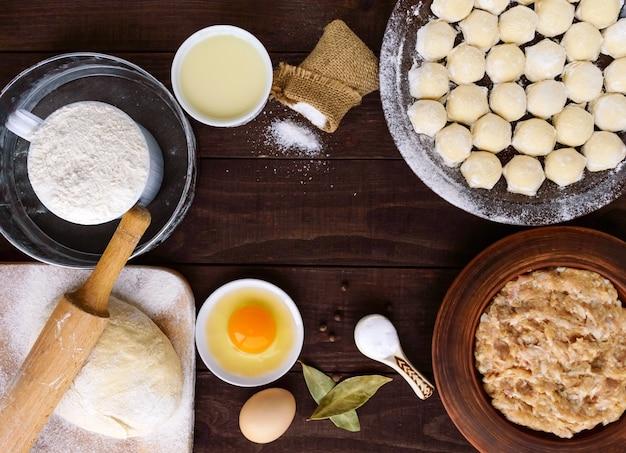 Piatto tradizionale russo - pelmeni (carne macinata succulenta con spezie nell'impasto). ingredienti per cucinare. la vista dall'alto.