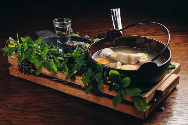 Zuppa di pesce tradizionale russa in una ciotola ukha servita con brace e vodka su tavola di legno brodo di pesce cucina tradizionale in russia