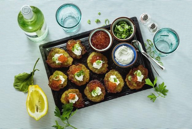 Frittelle di patate tradizionali russe servite con caviale rosso, cipolle verdi e panna acida su un vassoio con vino bianco e limone