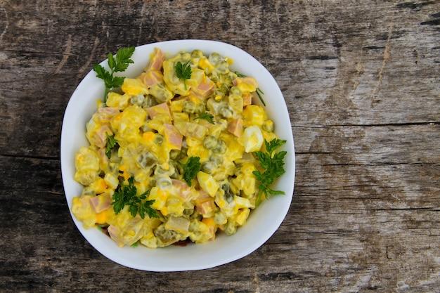 Olivier di insalata tradizionale russa con piselli, uova, cetrioli sottaceto, patate, salsicce e maionese sul tavolo di legno. vista dall'alto
